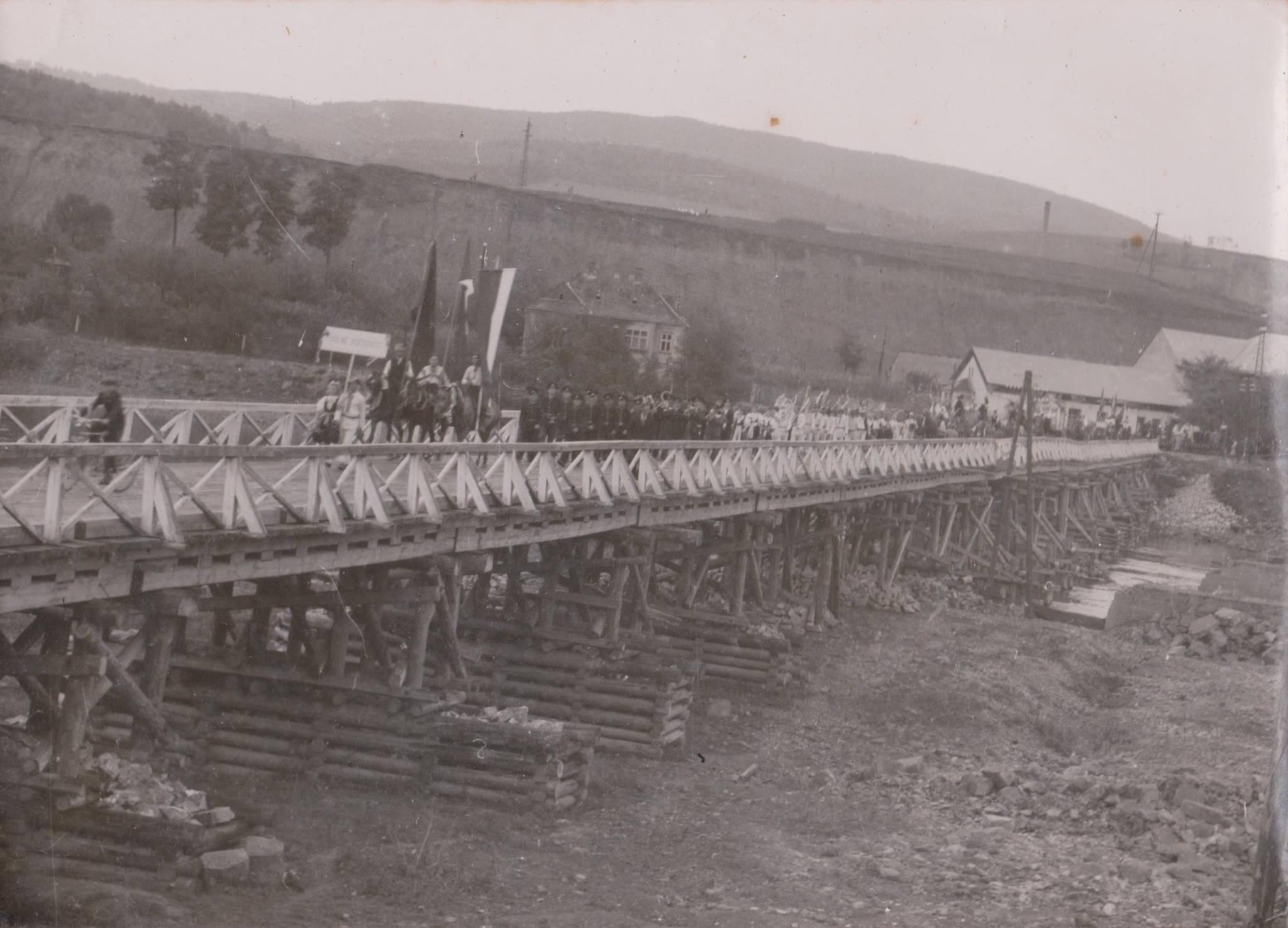 Fotograf zachytil okresnú dožinkovú slávnosť, ktorá sa konala 16. septembra 1945 - v sprievode na provizórnom drevenom moste cez Váh do Púchova sú obyvatelia Dolných Kočkoviec.