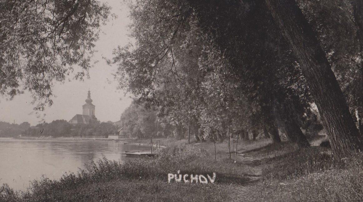 Pohľad na nábrežie Váhu pri Púchove z tzv. Horného parku v roku 1930. Pohľadnica od pána S. Mikulu zachytila pôvodné neregulované koryto Váhu, rovnako neprestavaný katol. kostol a malý prístav