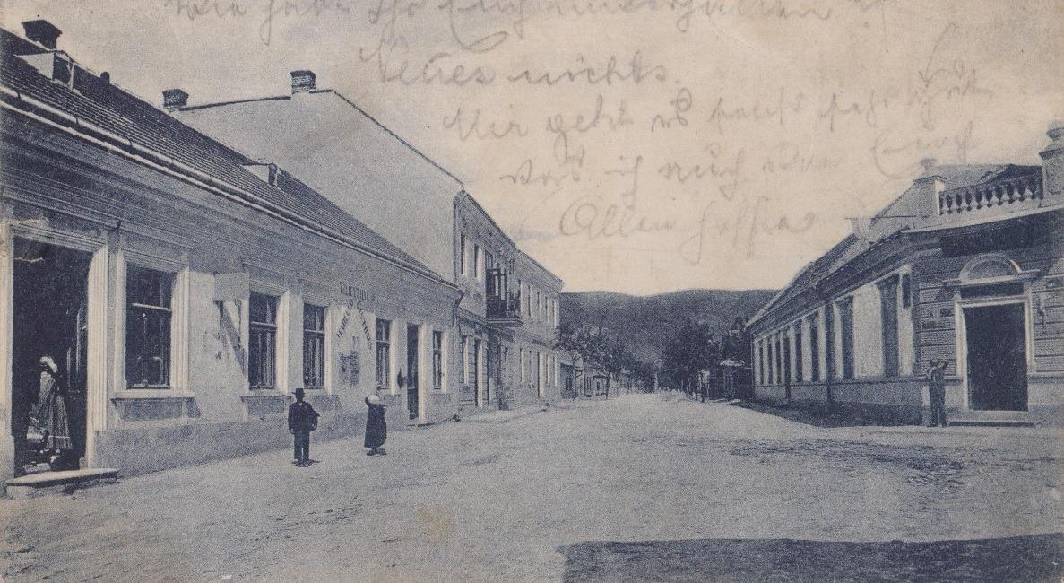 Pohľad na Moravskú ulicu v Púchove na začiatku 20. storočia: fotograf zachytil križovatku s dnešnou pešou zónou, pričom vľavo vidieť Hotel Lilienthal, za ním poschodovú budovu Židovskej školy a oproti na rohu dom obchodníka Nathana.