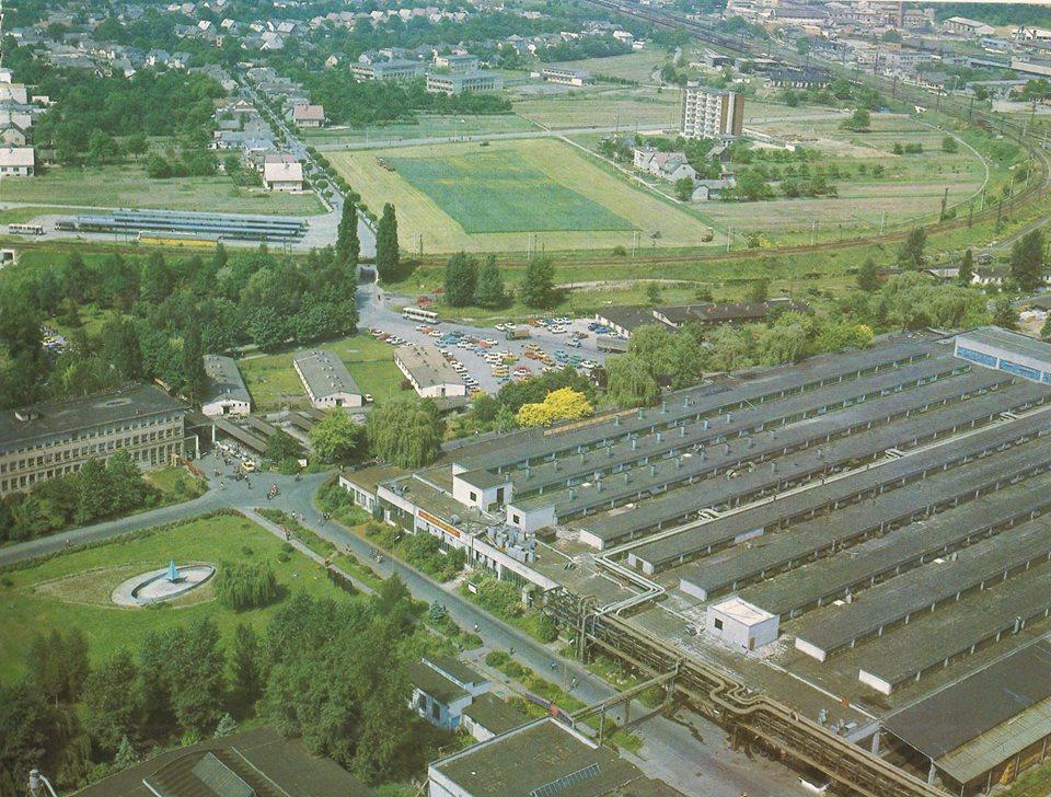 Fotografia zachytená pravdepodobne z vtedy najvyššej stavby v meste - komína: areál gumárenskej fabriky s fontánou, starou vstupnou bránou a v pozadí iba s jednou budovou tzv. slobodárok na začiatku 80. rokov minulého storočia
