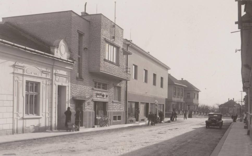 Na fotografii z 30. rokov minulého storočia vidieť dnešnú Hollého ulicu v Púchove, kde sa na jej oboch stranách nachádzali čerpacie stanice. Vo funkcionalistickej budove (stojí našťastie i dnes) vľavo bolo holičstvo s kaderníctvom a v budove oproti cez ulicu sa nachádzal Hotel u Patkovcov.