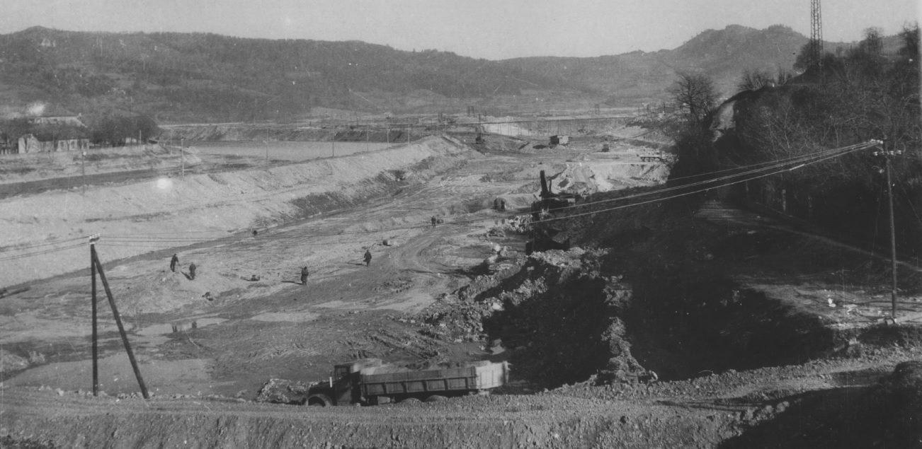 """Pohľad na úpravu odtokových pomerov rieky Váh pri Púchove z mosta: počas výstavby Priehrady mládeže v 50. rokoch minulého storočia bol vybudovaný i tzv. odpadový kanál (vzadu vpravo), ktorý sa vlieva späť do """"starého"""" koryta (vľavo). V mieste stretu týchto dvoch korýt Váhu bola vybudovaná betónová ostroha (v Púchove známa aj ako """"špic""""), ktorá usmerňuje naplaveniny (najmä štrk) pri usadzovaní sa na dne rieky."""