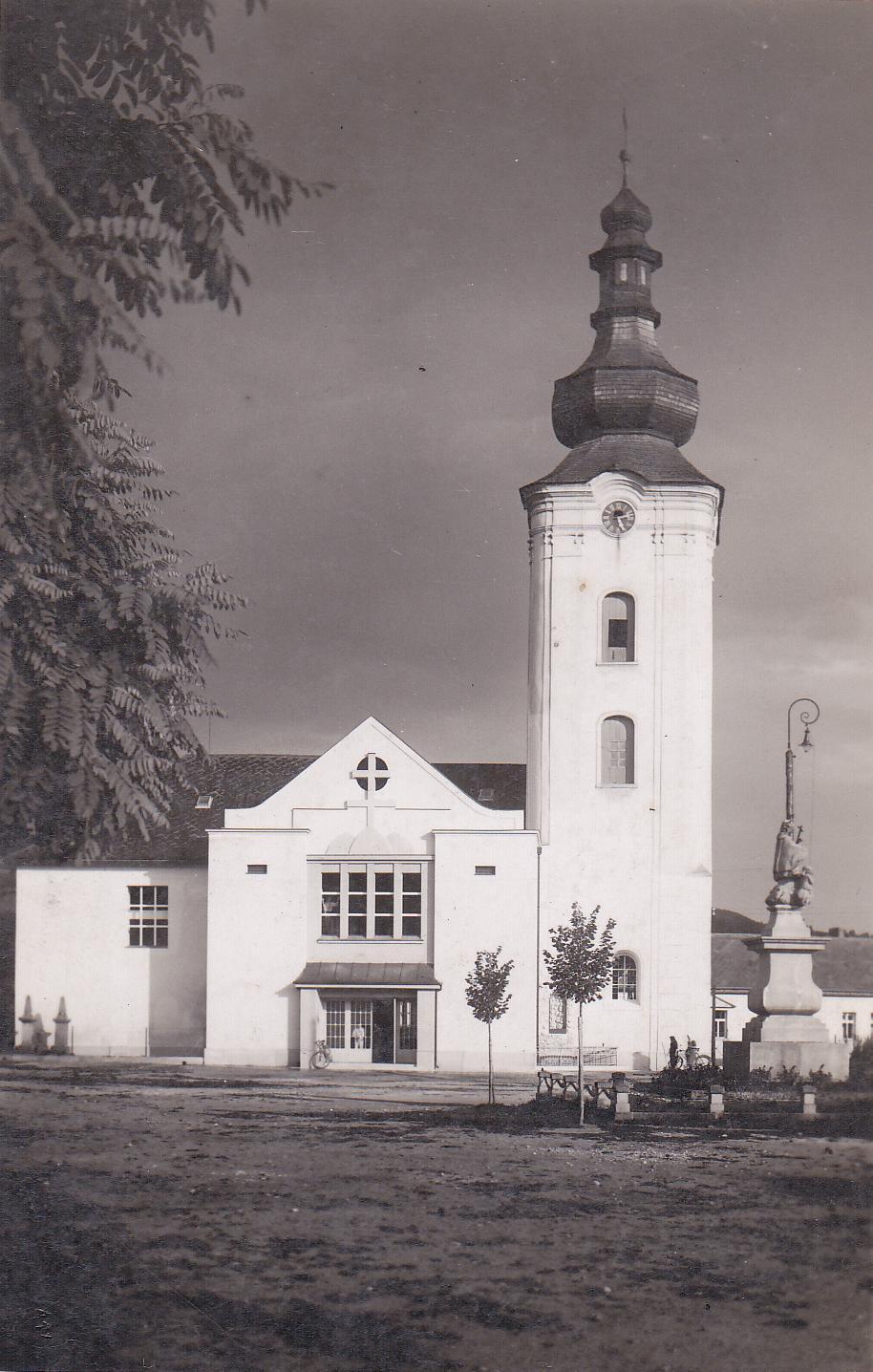 Námestie slobody v r. 1947 v Púchove: nedávno zasadené lipy a ohradenie okolo sochy sv. Jána Nepomuckého, dobové lampy,  čierne ciferníky na vežových hodinách