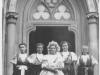 Krojované dievčatá (v strede svadobný) pred evanjelickým kostolom v  Púchove v r. 1904