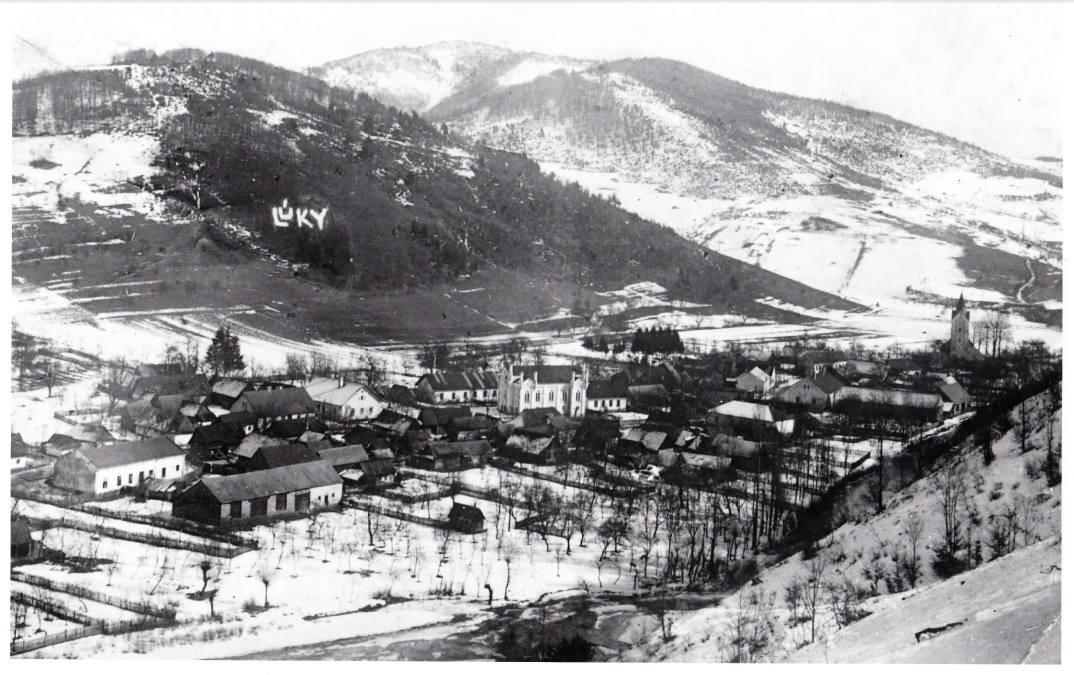 Zasnežená fotografiá z prelomu 20. a 30. rokov minulého storočia a na nej obec Lúky s dnes už neexistujúcou synagógou, ešte bez železničnej trate, bez cesty I. triedy č. 49...