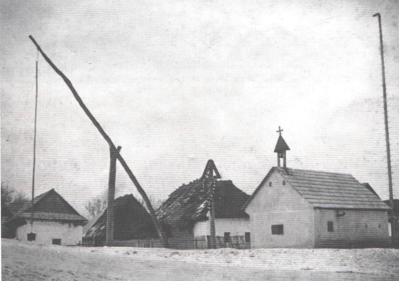 Požiarna zbrojnicu so zvonicou, krížom a vahadlovou studňou v roku 1900 v Dolných Kočkovciach